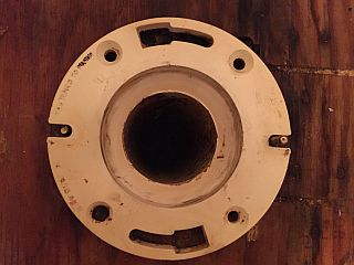 Photo of a floor flange for a toilet.