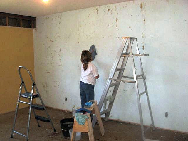 Photo of Frances, wife of Dave, preparing a wall for wallpapering.