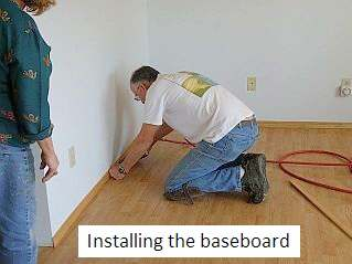 Photo of Dave installing the baseboard around hardwood floor.