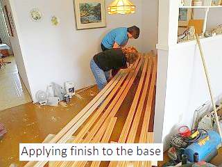 Photo of applying finish to the baseboard of hardwood floor.
