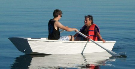 Photo of grandson of Dave rowing a sabot boat with his grandmother.