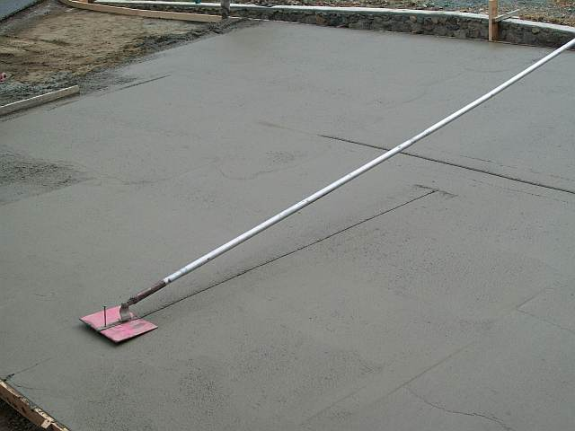 Photo of a concrete float being used to smooth the surface of the concrete driveway.