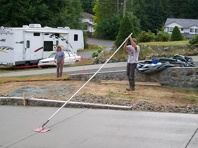 Photo of worker using the concrete float to smooth the surface of the concrete driveway.