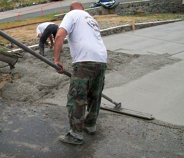 Photo of concrete worker using a bull float.