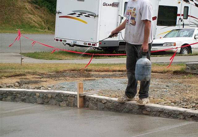 Photo of worker wetting the surface of the concrete driveway during the finishing stage.