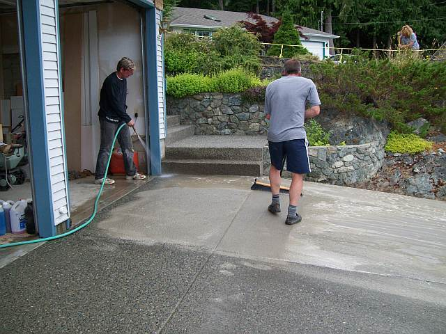 Photo of Dave sweeping away the wet surface of the concrete to expose the aggragate stones for the finish look of the driveway.