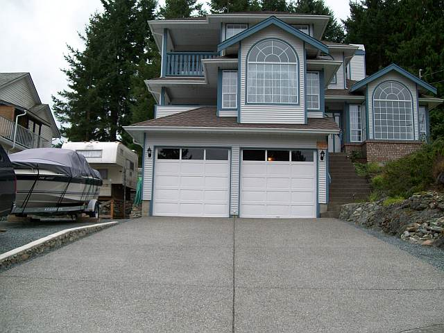 Photo of the front of Daves house showing the concrete driveway and curb.