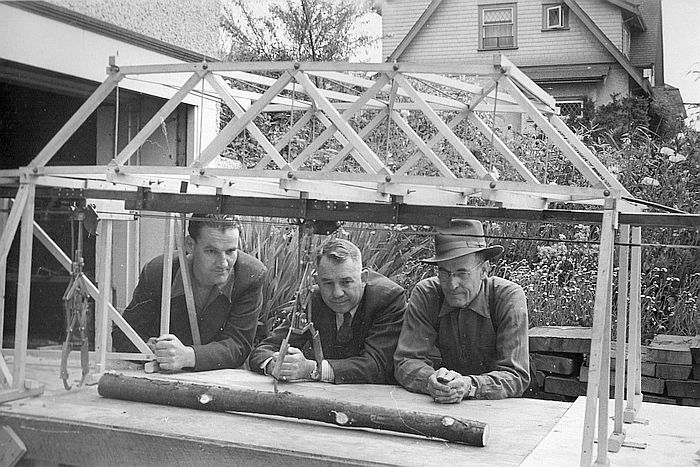 Photo of our Dad at the left, his foreman at the time and our grandfather looking at an invention of our Dad.