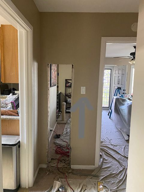 Photo of hallway in a house with drop cloths on floor and furniture.