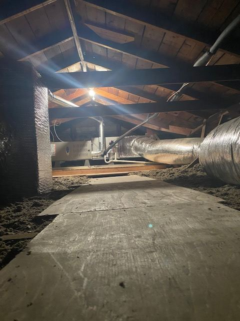Photo of attic with plywood partially covering floor.