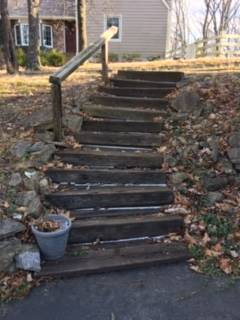 Photo of rotted boards in a backyard set of steps.